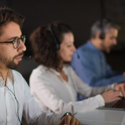Concentrated bearded call center operator working. Thoughtful call center operators during working process. Call center concept